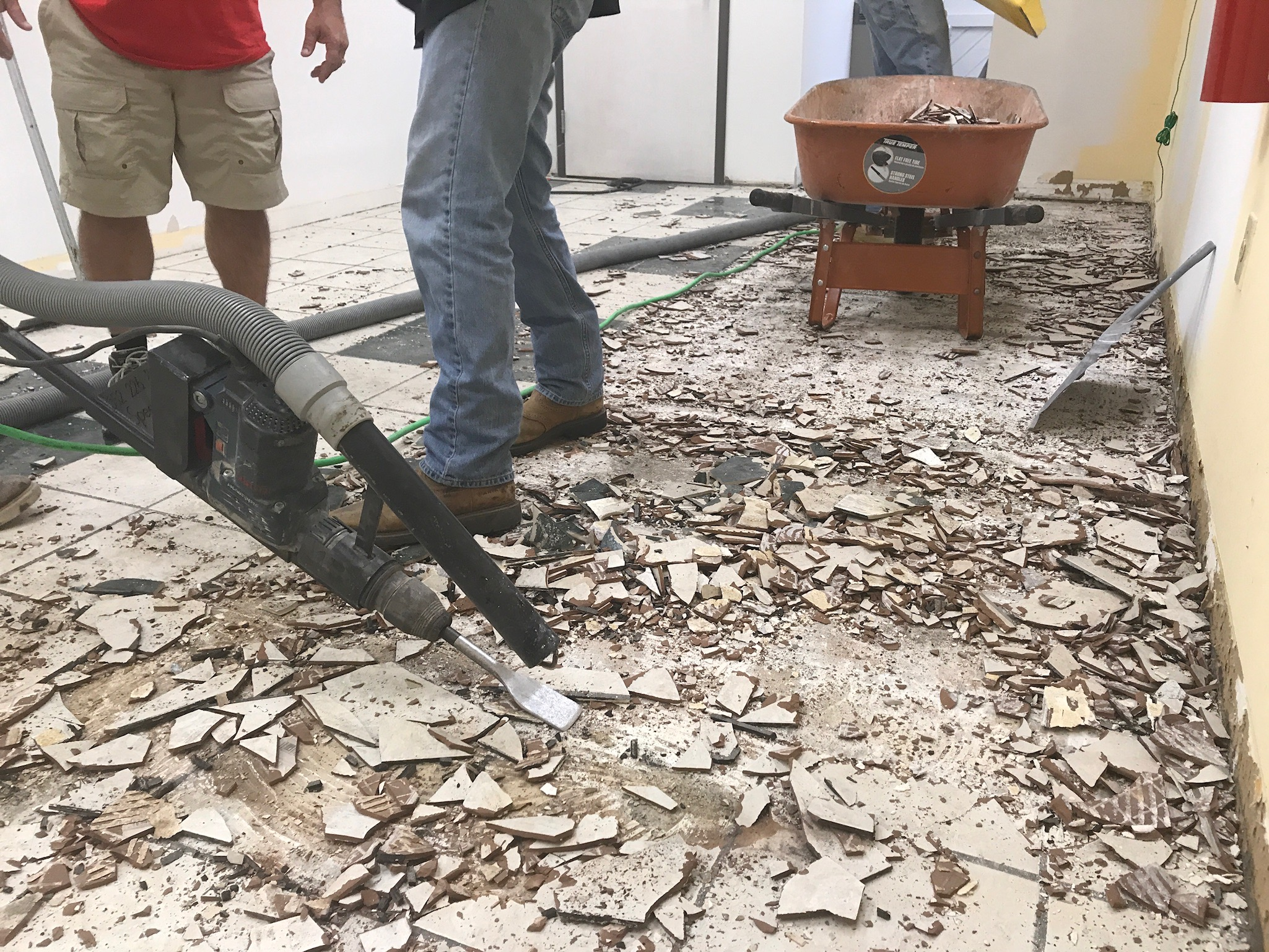 Image of tile floor removal while suctioning dust