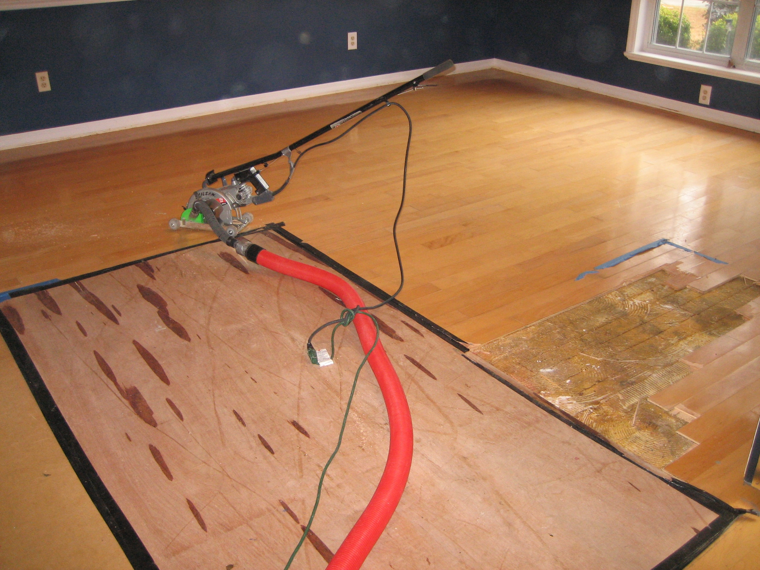 Image of wood floor being pried up with specialized machinery