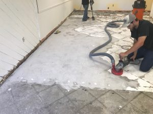 Speedy floor removal contractor grinds thinset off of a cement floor after removing tiles.