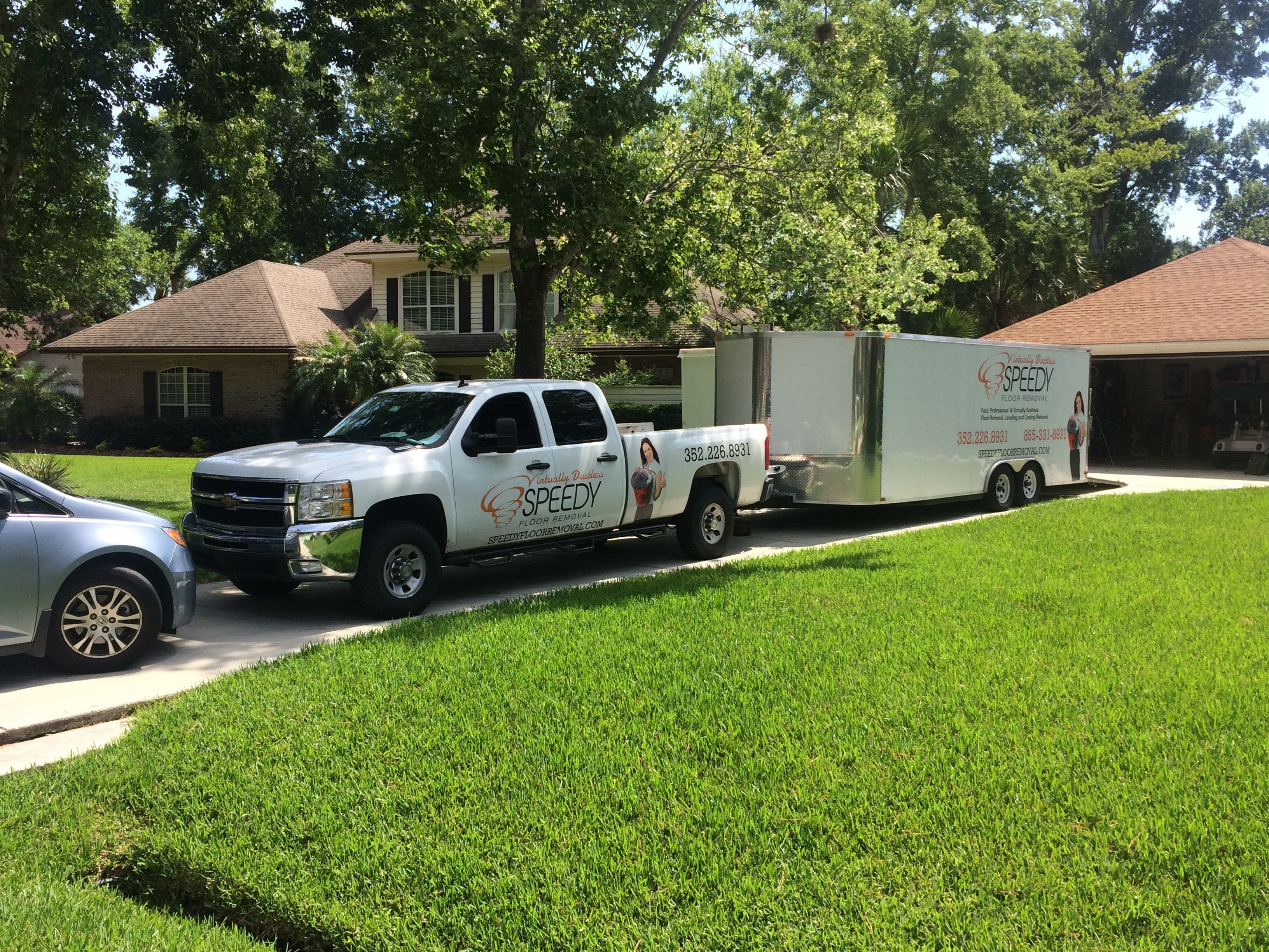 Image of a Speedy Floor Removal branded truck and trailer outside a residential home