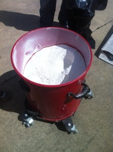Image of bucket of dust from dustless floor removal.