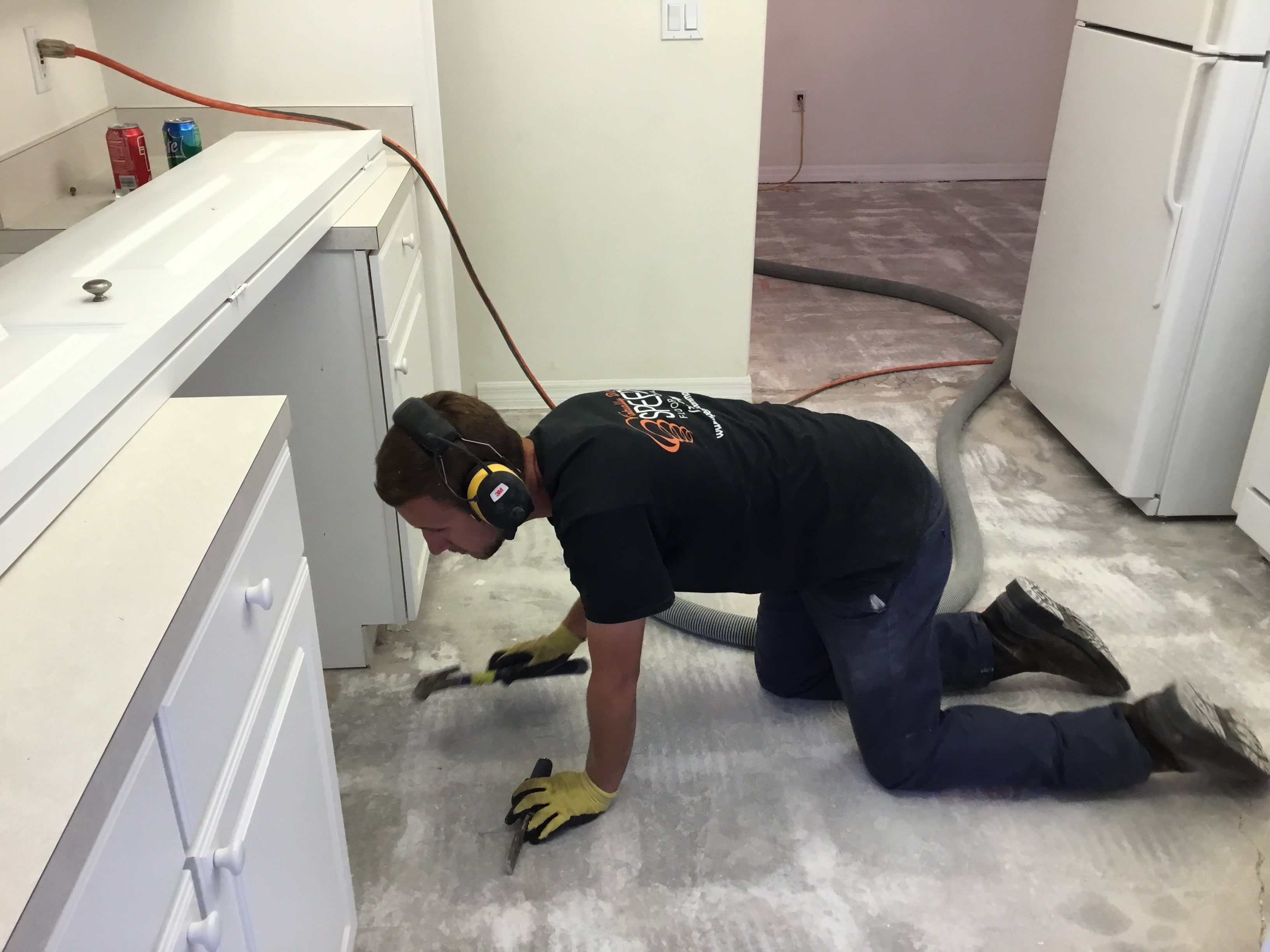 Image of a man vacuuming corners on a smooth sub-floor in the final stages of clean-up