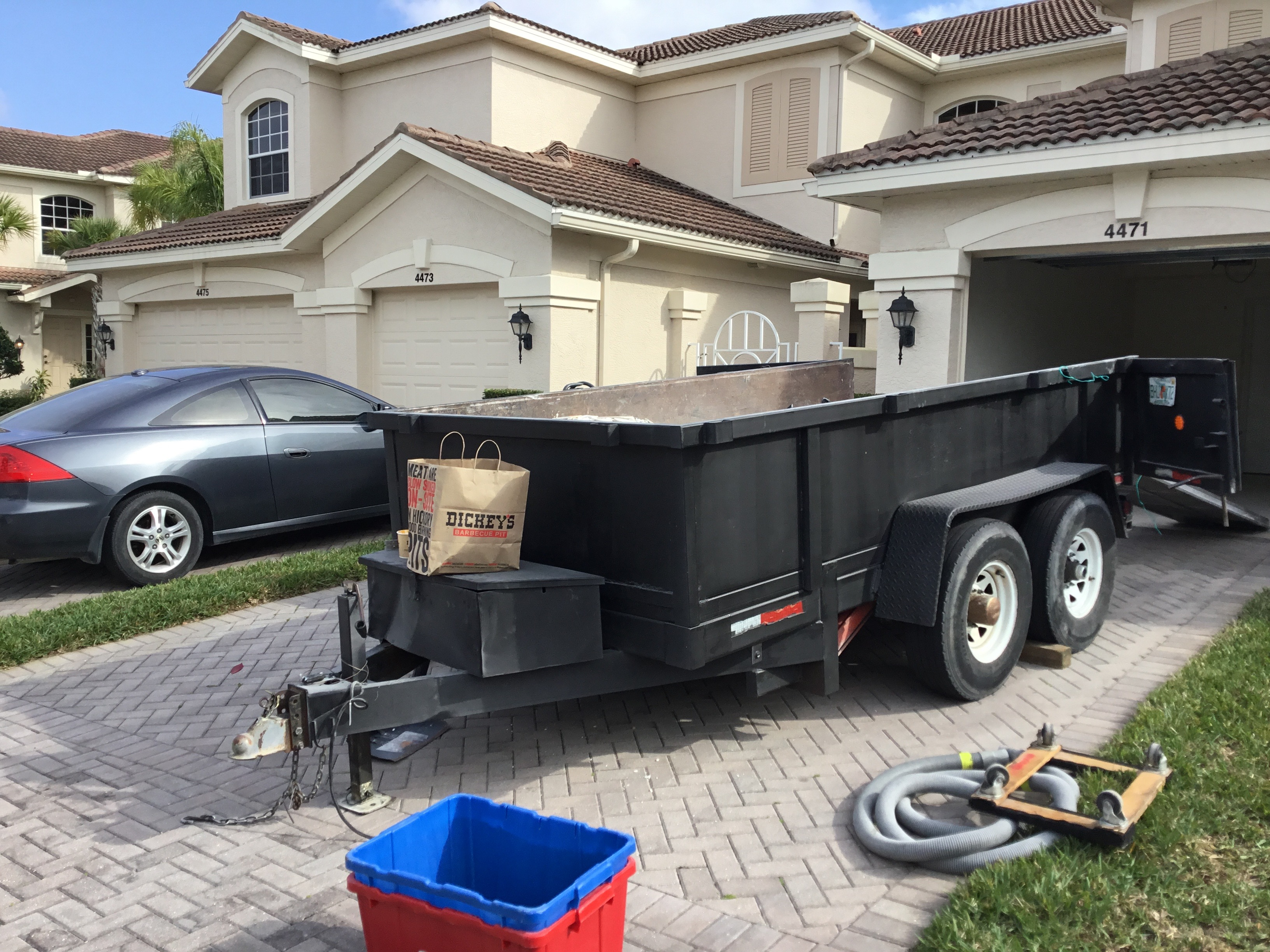 Image of Speedy Floor Removal dump trailers parked outside a North Florida home