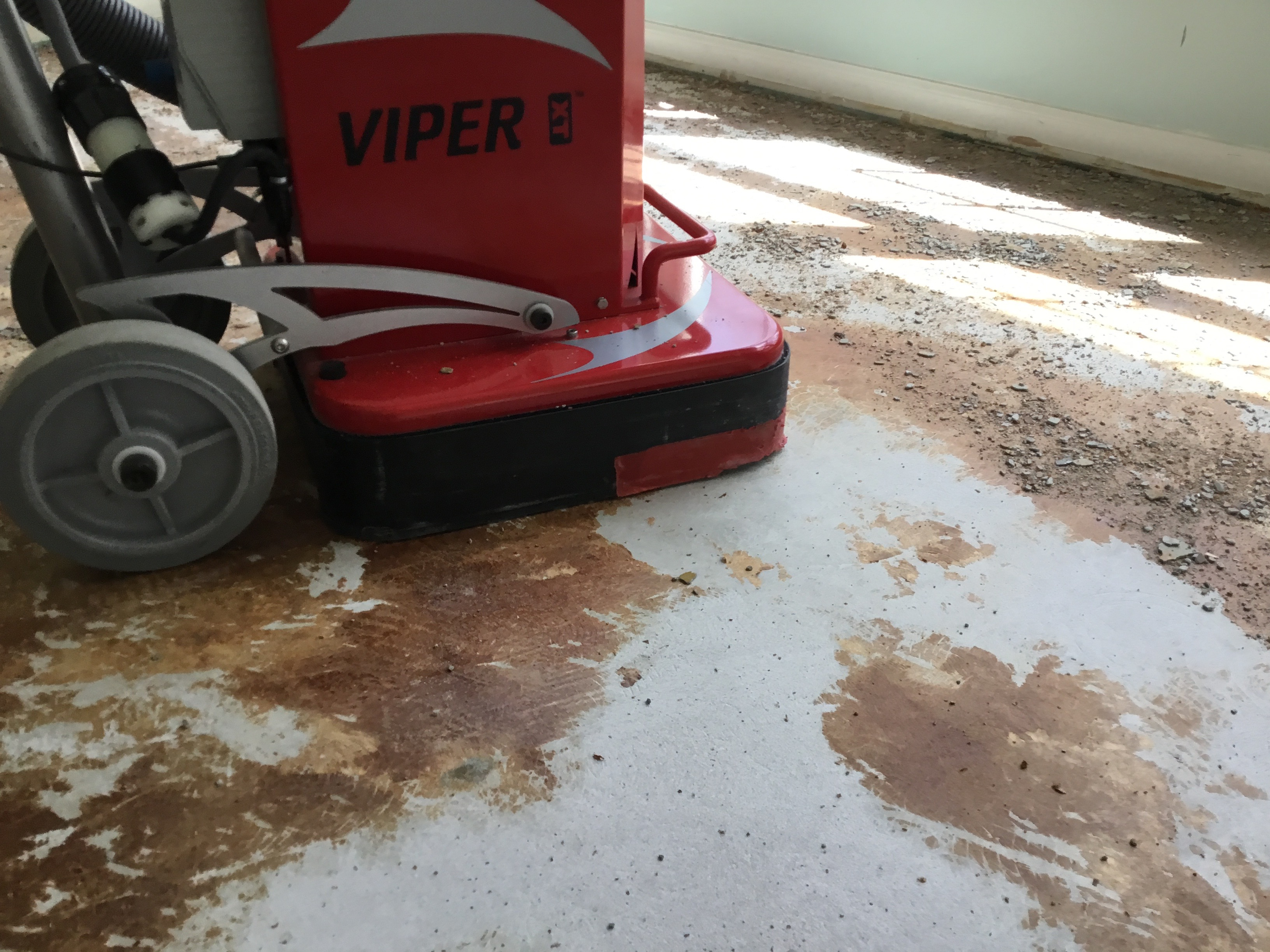Close-up image of wood floor glue removal from concrete subfloor