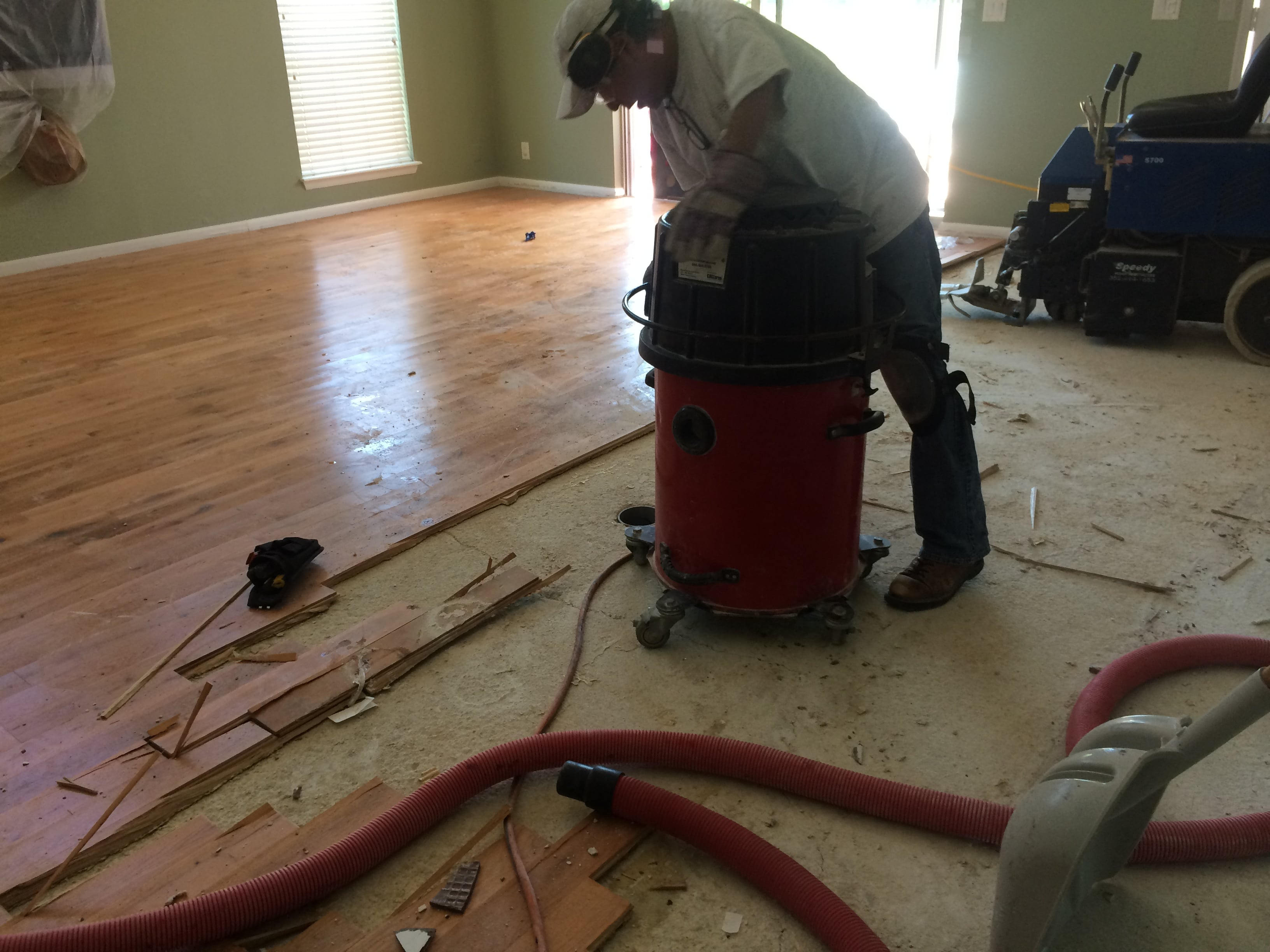 Image of wood floor removal revealing concrete subfloor underneath